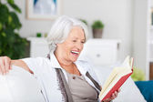 Laughing senior woman reading an amusing book — Stock Photo