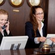 Two receptionists at a reception desk — Stock Photo