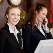 Two women working as professional receptionists — Stock Photo