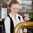 Stock Photo: Happy barmaid pouring draft beer