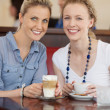 Two happy female friends enjoying a cup of cofee — Stock Photo