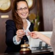 Beautiful receptionist handing over a card — Stock Photo #29708775
