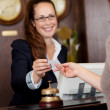 Beautiful receptionist handing over a card — Stock Photo