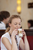 Woman daydreaming while drinking a late macchiato — Stock Photo