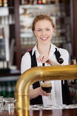 Smiling barmaid serving draft beer — Stock Photo