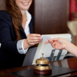 Female receptionist passing card — Stock Photo