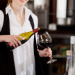 Улыбаясь официантка, наливание стакан красного вина — Стоковое фото
