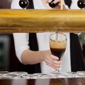 Waitress pouring dark beer — Stock Photo