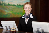 Happy woman working as a receptionist in a hotel — Stock Photo
