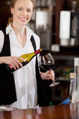 Smiling waitress pouring a glass of red wine — Stock Photo