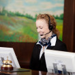 Smiling receptionist wearing a headset — Stock Photo