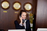 Happy receptionist talking on a telephone — Stock Photo