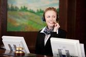 Jovem mulher que trabalha na recepção de um hotel — Foto Stock