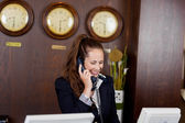 Smiling receptionist taking a telephone call — Stock Photo