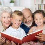 Elderly couple reading to their grandchildren — Stock Photo