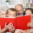 Grandchildren reading with their grandparents — Stock Photo