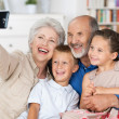 Grandparents and grandchildren with a camera — Stock Photo
