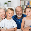 Happy young siblings with their grandparents — Stock Photo