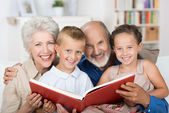 Elderly couple reading to their grandchildren — Stock Photo