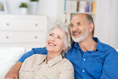 Contented elderly couple sitting reminiscing — Stock Photo
