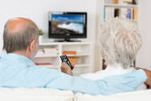 Elderly couple watching television — Stock Photo