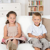 Little brother and sister sitting on a couch — Stock Photo