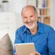 Elderly man holding a tablet-pc — Stock Photo