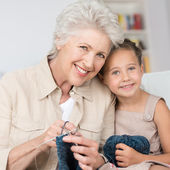 Grandmother teaching her granddaughter to knit — Stock Photo