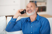 Delighted senior man chatting on a mobile phone — Stock Photo