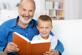 Grandad and grandson enjoying a book together — Stock Photo