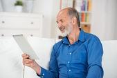 Homem idoso ler a tela do seu tablet pc — Fotografia Stock
