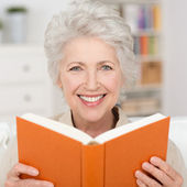 Attractive senior woman reading a book — Stock Photo