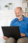 Pensioner working on a laptop at home — Stock Photo