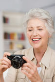 Happy senior woman setting her compact camera — Stock Photo