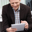 Smiling man using a tablet-pc — Stock Photo #31019329