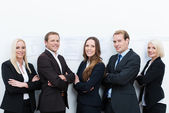 Happy professional team standing with folded arms — Stock Photo