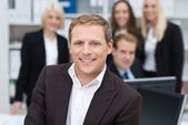 Confident businessman backed by his team — Stock Photo