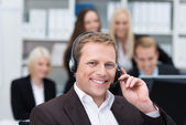 Smiling businessman using a headset — Stock Photo
