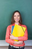 Friendly student or teacher clutching a her files — Stock Photo