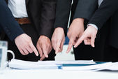 Group of businesspeople pointing to a document — Stock Photo