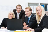 Smiling business team at work in the office — Stock Photo