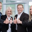 Successful business team giving a thumbs up — Stock Photo