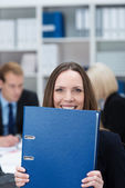 Playful businesswoman holding a large folder — Stock Photo