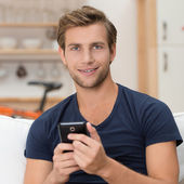 Young man holding a smartphone — Stock Photo
