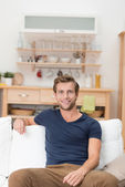 Handsome youn man sitting on a sofa — Stock Photo