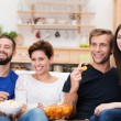 Laughing group of friends watching television — Stock Photo