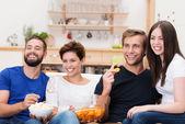 смеющийся группа друзей, смотреть телевизор — Стоковое фото