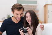 Happy couple checking a photo on their camera — Stock Photo