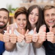 Young men and women giving a thumbs up — Stock Photo