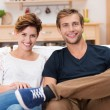 Smiling young couple on a sofa — Foto Stock